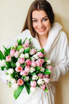 Een meisje met een oprechte glimlach heeft een prachtig boeket tulpen in haar hand. natuurlijke schoonheid. lente bruid boeket. fijne vrouwendag.