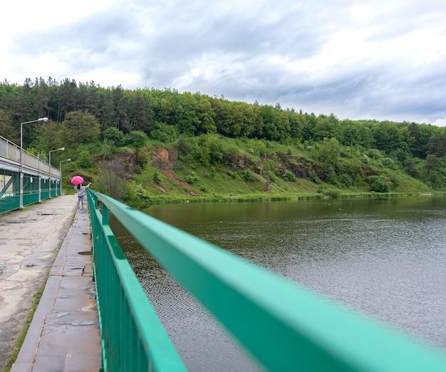 Een meisje met een paraplu bij bewolkt weer voor een wandeling in het bos, staat op een brug tegen de achtergrond van een landschap