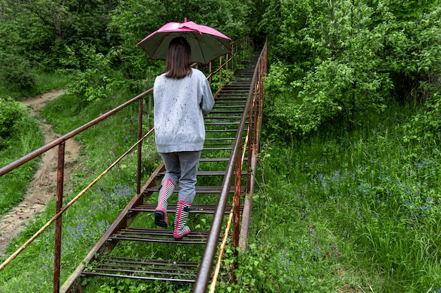 Een meisje met een paraplu loopt in het bos bij regenachtig weer