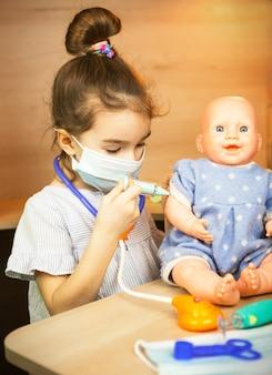 Een meisje met een pop speelt dokter, maakt een spuitinenting in de hand. vaccinatie, vaccinatiekalender, vaccin, beroepsspel. de injectie van de verpleegster