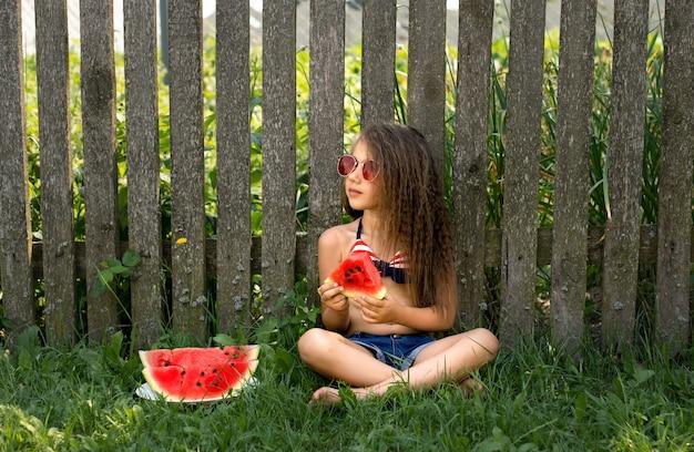 Een meisje met een rode bril zit bij een oud hek en eet bedachtzaam een watermeloen