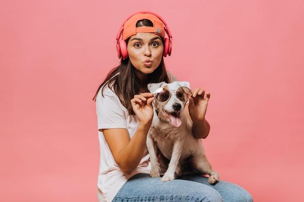 Een meisje met een roze koptelefoon op haar hoofd en een oranje baseballpet, gekleed in een lichtroze t-shirt en een spijkerbroek, zet een zonnebril op de hond die op haar schoot zit
