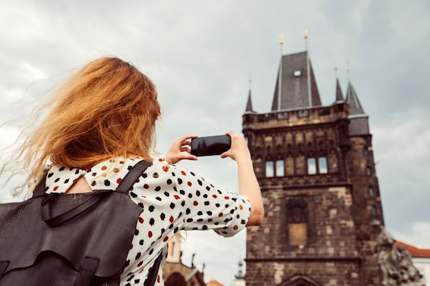 Een meisje met een rugzak maakt een foto aan de telefoon van de karelsbrug van praag. toeristische meisje maakt foto's van de praagse burcht. een vrouw heeft een smartphone in haar handen.