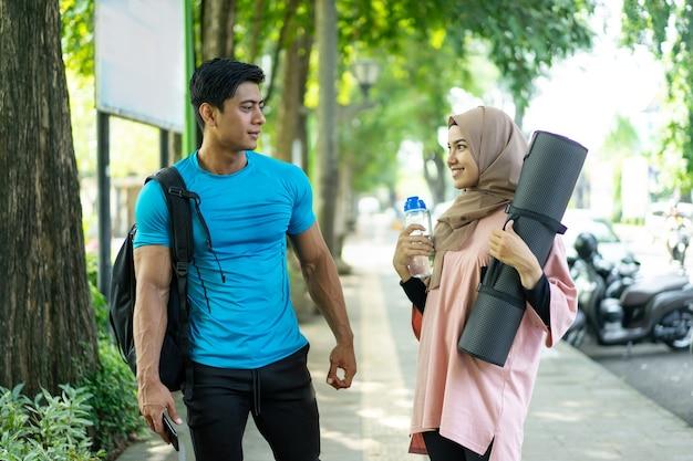 Een meisje met een sluier brengt een matras en een drinkfles en een man draagt een rugzak als hij buitensporten in het park doet