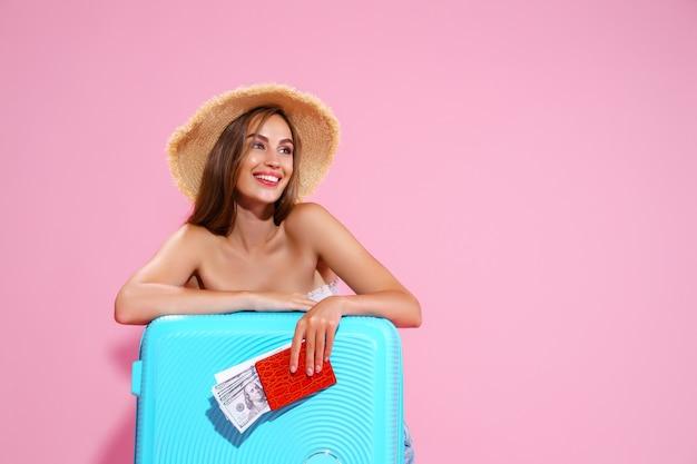 Een meisje met een strooien hoed houdt kaartjes in haar handen een reis een tas