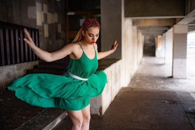 Een meisje met een verbaasd gezicht met heldere vlechten en regenboogglittermake-up in een lichtgroene lentejurk. springen van de trappen van een groot oud gebouw in een warme lentestad.