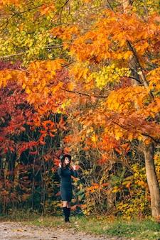 Een meisje met een welgevormde figuur houdt haar hoed met haar handen vast en kijkt naar de toppen van vergeelde bomen