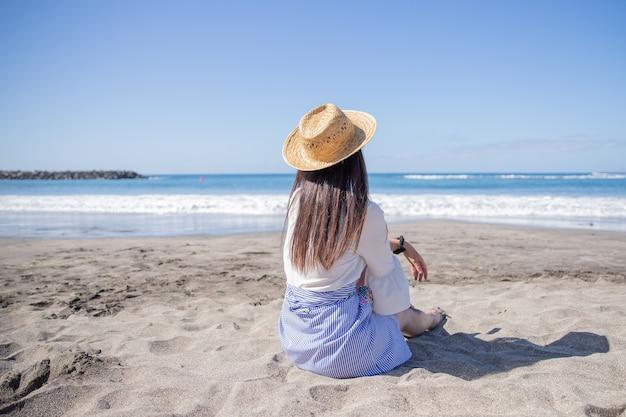 Een meisje met een zomerhoed zit op het strand en geniet van het uitzicht op zee