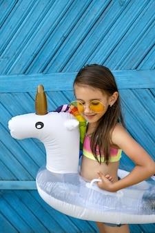 Een meisje met een zonnebril staat tegen een blauwe muur met een cirkel in de vorm van een eenhoorn