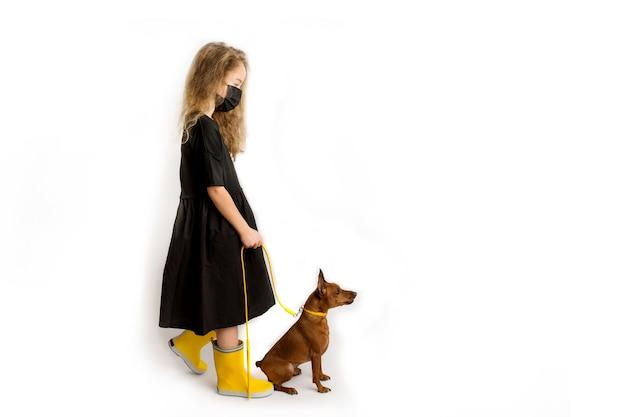 Een meisje met een zwart beschermend antiviraal masker laat de hond uit. nieuwe realiteit van het leven tijdens de covid-19-pandemie. voorzorgsmaatregelen voor pandemie van het coronavirus. reizen met huisdieren. hoge kwaliteit foto