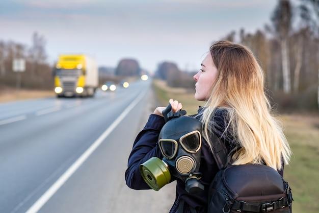 Een meisje met een zwart gasmasker op zijn schouder staat aan de rand van een snelweg in een buitenwijk