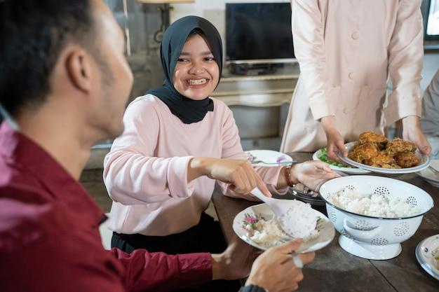 Een meisje met een zwarte hoofddoek serveert tijdens de lunch rijst aan haar vriendje