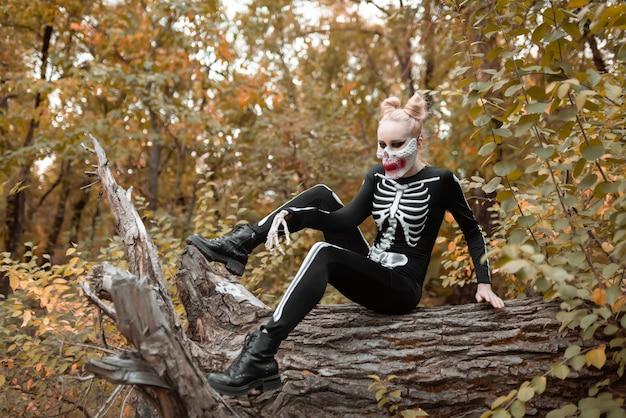 Een meisje met enge make-up in een skeletkostuum zit op een verdorde oude boom. halloween