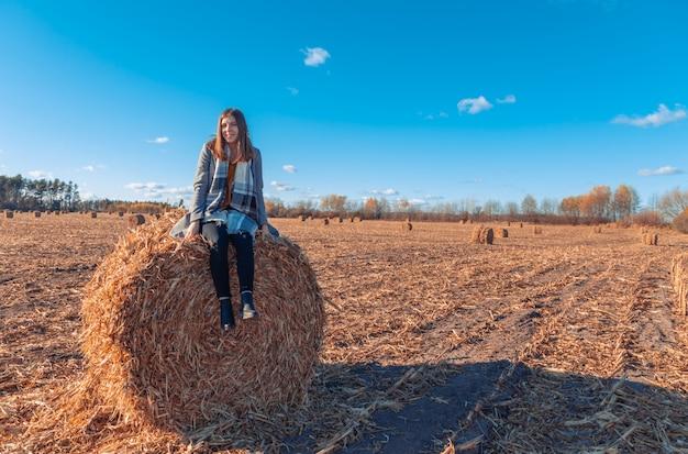 Een meisje met europese uitstraling in een grijze jas staat in een veld bij een grotere baal met hooi tegen een blauwe hemel.