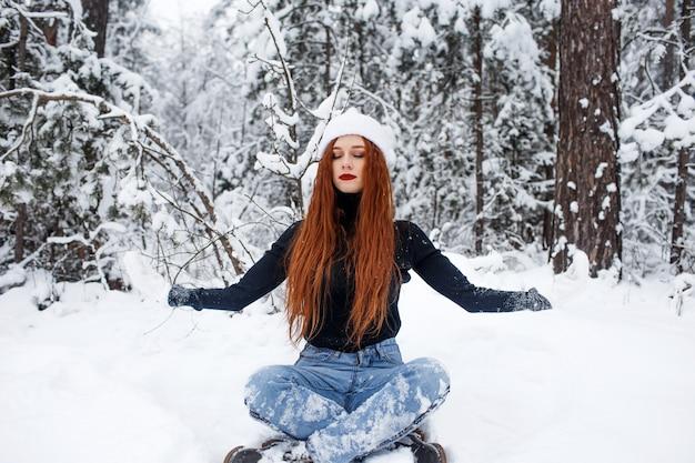 Een meisje met fel rood haar mediteert zittend in het bos. ontspannen in de natuur.