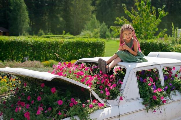 Een meisje met frican-roze staartjes van kanekalon zit op een designauto met bloemen