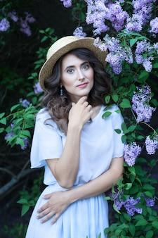 Een meisje met golvend bruin haar in een strohoed in een lila tuin in bloei mooi meisjesportret allergie zomervakantie tuinieren vrouwelijkheid