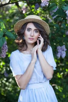 Een meisje met golvend bruin haar in een strohoed in een lila tuin in bloei vrouwelijkheid zomervakantie