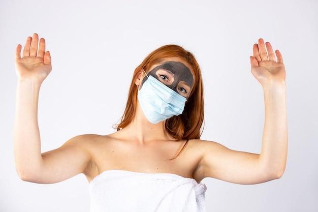 Een meisje met haar handen omhoog, met een cosmetisch masker op haar gezicht en een ander van een pandemie, kijkt zijwaarts op. beauty, spa, gezondheid en covid 19-concept. hoge kwaliteit foto