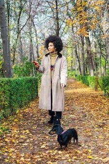 Een meisje met haar hond wandelen in het park, luisteren naar muziek met een koptelefoon