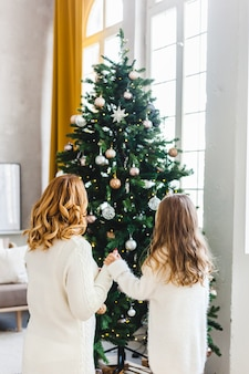 Een meisje met haar moeder bij de kerstboom, het interieur versierd voor kerstmis, familie en vreugde, tradities