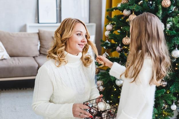 Een meisje met haar moeder in de buurt van de kerstboom, het interieur ingericht voor het nieuwe jaar en kerstmis, familie en vreugde, tradities