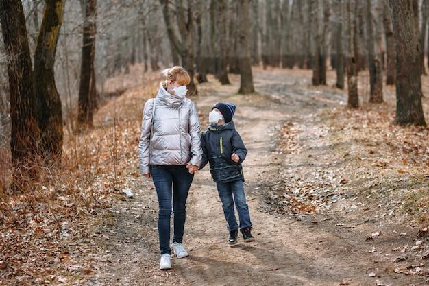 Een meisje met haar zoon in sanitaire maskers op een wandeling in het park