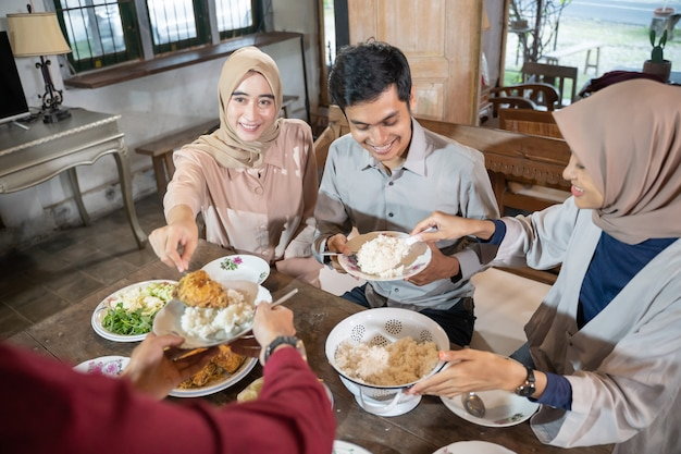 Een meisje met hijab geeft tijdens de lunch gebakken kip aan haar vriendje