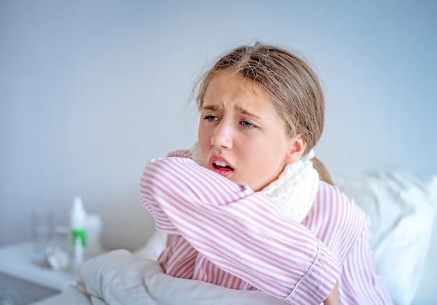 Een meisje met koorts zit op bed en hoest in haar elleboog