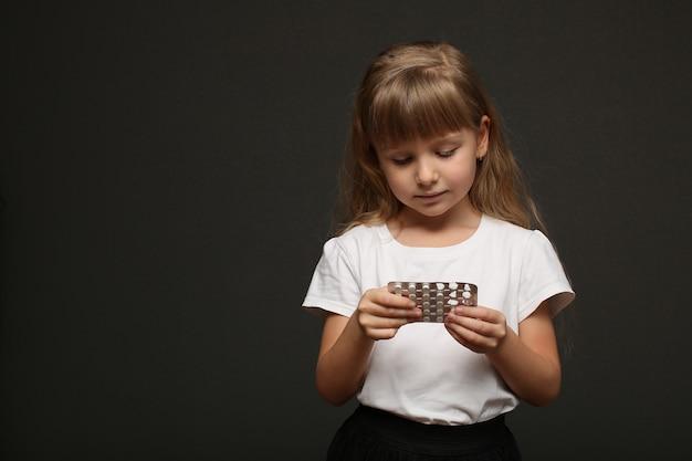 Een meisje met lang blond haar houdt pillen in haar handen en kijkt ernaar.
