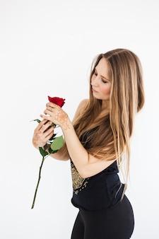Een meisje met lang blond haar in donkere kleren met een roos in haar hand, schoonheid, zelfverzorging, henna puttend uit haar handen, tradities