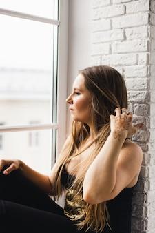 Een meisje met lang blond haar in donkere kleren, zittend bij een raam, thuis, quarantaine, gedachten over de toekomst, isolatie, schoonheid