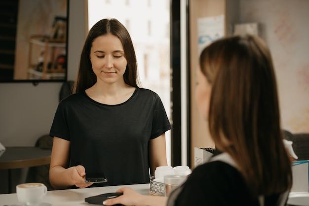 Een meisje met lang haar betaalt voor haar koffie met een smartphone door contactloze nfc-technologie in een café. een vrouwelijke barista reikt een cliënt een betaalterminal aan.