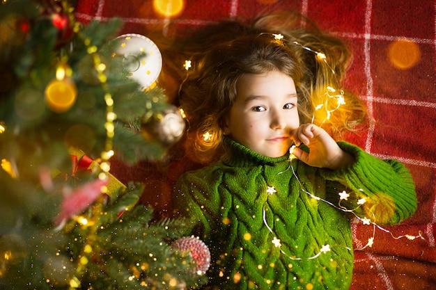 Een meisje met lang haar en slingers ligt op een rode plaid onder een kerstboom met speelgoed in een warme gebreide trui. kerstmis, nieuwjaar, emoties van kinderen, vreugde, verwachting van een wonder en geschenken