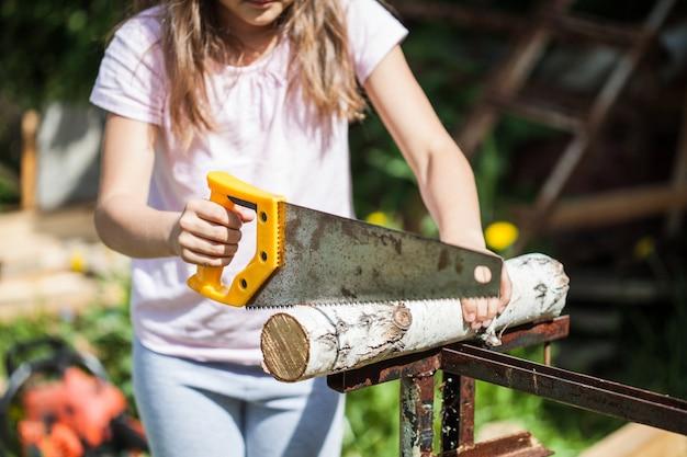Een meisje met lang haar helpt ouders in de zomer, zaagt een houtblok met een zaag, hout, constructie, brandhout, kachel, spel, training