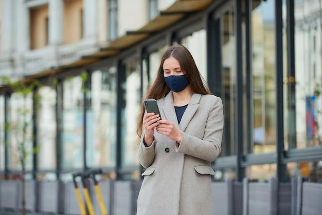 Een meisje met lang haar in een marineblauw gezichtsmasker om de verspreiding van het coronavirus te voorkomen, gebruikt een smartphone op straat. een vrouw in gezichtsmasker tegen covid-19 draagt een jas en leest nieuws op een mobiel in de stad