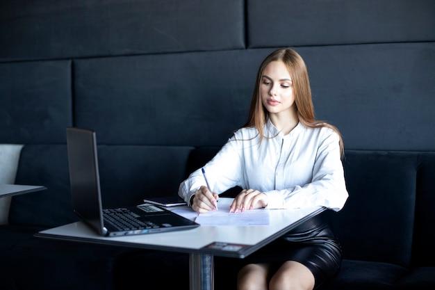 Een meisje met lang haar in een wit overhemd vult documenten in