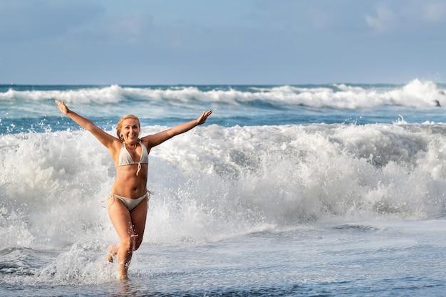 Een meisje met nat haar springt over grote golven in de atlantische oceaan, rond een golf met spetters spray en waterdruppels.