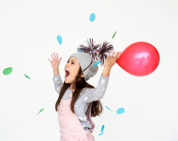 Een meisje met rode ballon met plezier