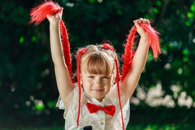 Een meisje met rode staartjes in de natuur in de zomer. een kind in een pak met een vlinderdas. hoge kwaliteit foto