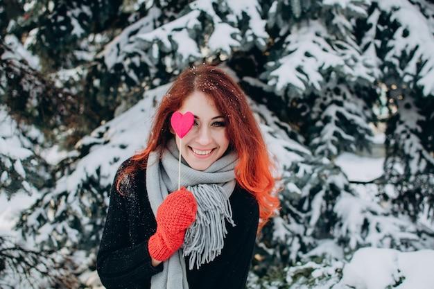 Een meisje met rood haar houdt een hart op een stok in haar handen tegen een achtergrond van bomen en sneeuw