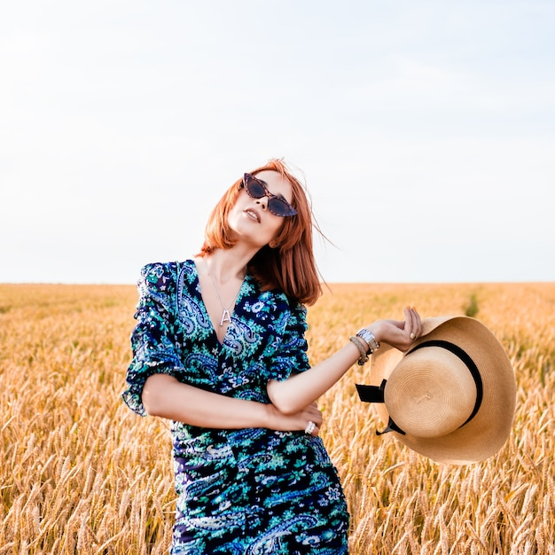 Een meisje met rood haar staat in een veld