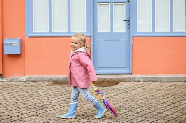 Een meisje met rubberen laarzen en een paraplu loopt op de stoep