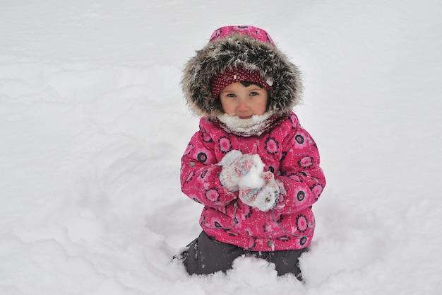 Een meisje met sneeuw in haar handen. een kind in winterkleren, spelen met sneeuw.