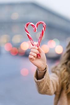 Een meisje met snoepgoed in de vorm van een hart tegen de achtergrond van wazige stadslichten.