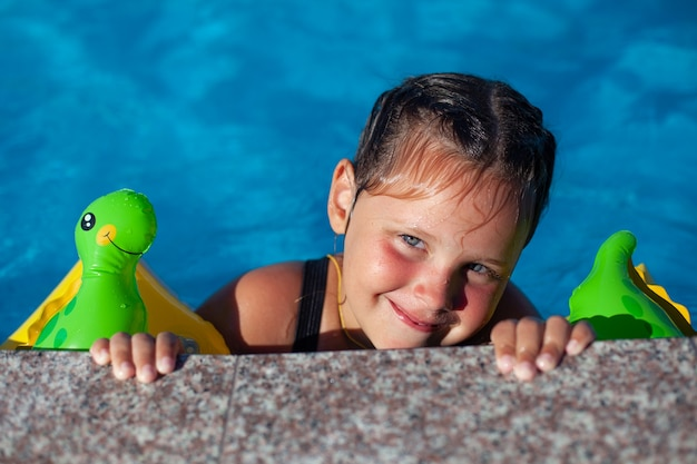 Een meisje met staartjes heeft een goede tijd in het hotel op een zonnige warme dag op het strand