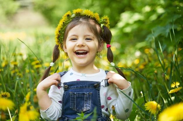 Een meisje met twee staarten zit in een veld van paardebloemen.
