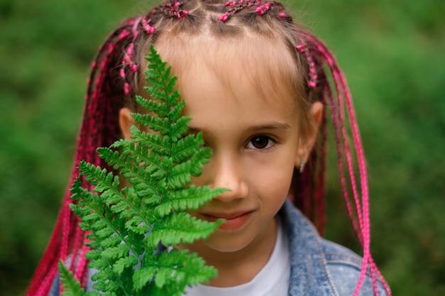 Een meisje met zizi afropigtailed dreadlocks bedekt oog met een varenblad
