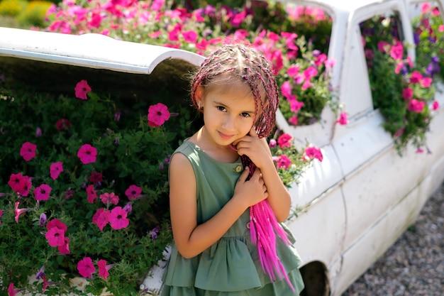 Een meisje met zizi-vlechtjes van kanekalon staat bij een decoratieve auto met bloemen erin