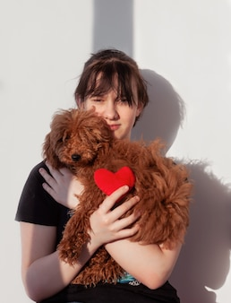 Een meisje met zwart haar knuffelt een ruige roodbruine poedelhond en houdt een rood hart in haar hand.
